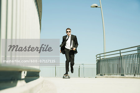 Businessman skateboarding on walkway holding binder, Germany Stock Photo - Premium Royalty-Free, Image code: 600-07117115