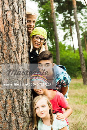 Portrait of group of children posing next to tree in park, Germany Stock Photo - Premium Royalty-Free, Image code: 600-07117117