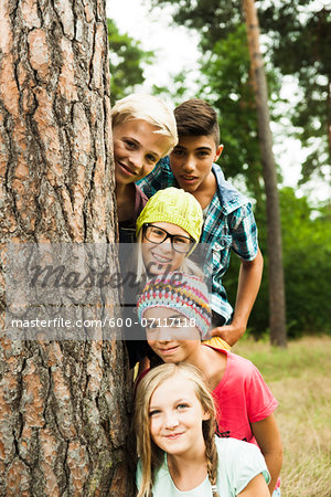 Portrait of group of children posing next to tree in park, Germany Stock Photo - Premium Royalty-Free, Image code: 600-07117118