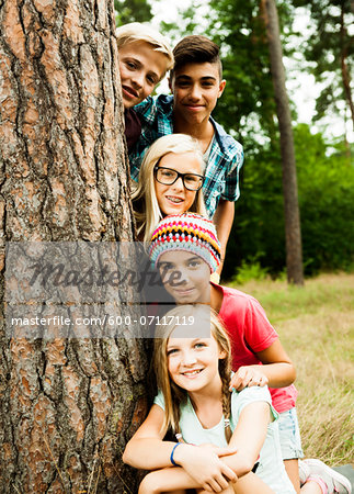 Portrait of group of children posing next to tree in park, Germany Stock Photo - Premium Royalty-Free, Image code: 600-07117119