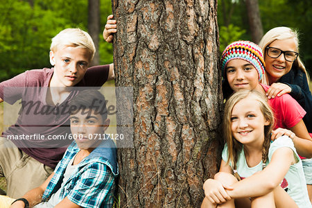 Portrait of group of children posing next to tree in park, Germany Stock Photo - Premium Royalty-Free, Image code: 600-07117120