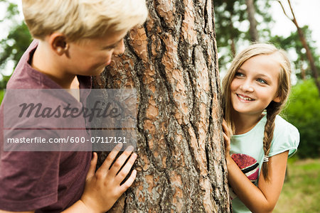Boy and Girl playing outdoors standing next to tree in park, Germany Stock Photo - Premium Royalty-Free, Image code: 600-07117121