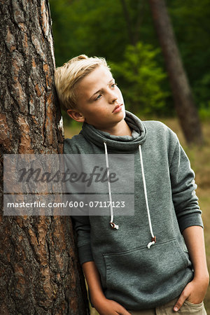 Portrait of boy standing in front of tree in park, looking into the distance, Germany Stock Photo - Premium Royalty-Free, Image code: 600-07117123
