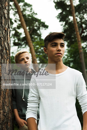 Portrait of two boys standing next to tree in park, Germany Stock Photo - Premium Royalty-Free, Image code: 600-07117124