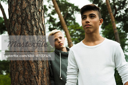 Portrait of two boys standing next to tree in park, Germany Stock Photo - Premium Royalty-Free, Image code: 600-07117125