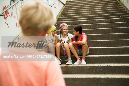 Backview of boy watching girls sitting on stairs outdoors, Germany Stock Photo - Premium Royalty-Free, Image code: 600-07117156