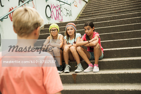 Backview of boy approaching girls sitting on stairs outdoors, Germany Stock Photo - Premium Royalty-Free, Image code: 600-07117157