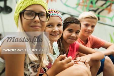 Close-up of group of children sitting on stairs outdoors, looking at camera, Germany Stock Photo - Premium Royalty-Free, Image code: 600-07117158