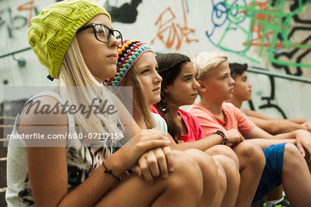 Group of children sitting on stairs outdoors, looking forward in the same direction, Germany Stock Photo - Premium Royalty-Free, Image code: 600-07117159
