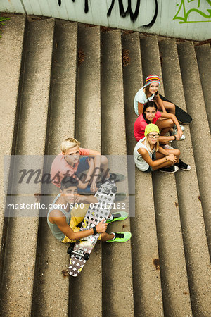 Group of children sitting on stairs outdoors, looking up at camera, Germany Stock Photo - Premium Royalty-Free, Image code: 600-07117162