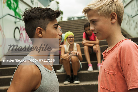 Two boys standing face to face, group of children sitting on stairs in background, Germany Stock Photo - Premium Royalty-Free, Image code: 600-07117166