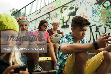 Group of children sitting on stairs outdoors, using tablet computers and smartphones, Germany Stock Photo - Premium Royalty-Free, Image code: 600-07117168