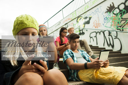 Group of children sitting on stairs outdoors, using tablet computers and smartphones, Germany Stock Photo - Premium Royalty-Free, Image code: 600-07117169