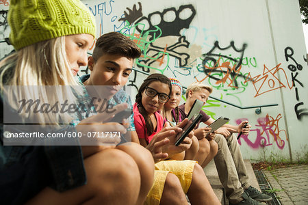 Group of children sitting on stairs outdoors, using tablet computers and smartphones, Germany Stock Photo - Premium Royalty-Free, Image code: 600-07117171