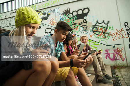Group of children sitting on stairs outdoors, using tablet computers and smartphones, Germany Stock Photo - Premium Royalty-Free, Image code: 600-07117172