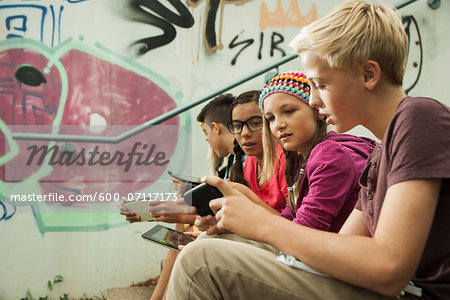 Group of children sitting on stairs outdoors, using tablet computers and smartphones, Germany Stock Photo - Premium Royalty-Free, Image code: 600-07117173