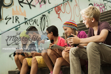 Group of children sitting on stairs outdoors, using tablet computers and smartphones, Germany Stock Photo - Premium Royalty-Free, Image code: 600-07117174