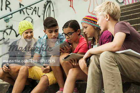 Group of children sitting on stairs outdoors, using tablet computers and smartphones, Germany Stock Photo - Premium Royalty-Free, Image code: 600-07117175