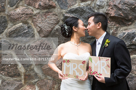 Portrait of Married Couple with Mr and Mrs Signs Stock Photo - Premium Royalty-Free, Image code: 600-07117236