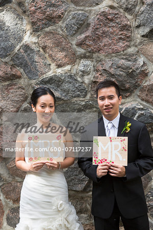 Portrait of Married Couple with Mr and Mrs Signs Stock Photo - Premium Royalty-Free, Image code: 600-07117237