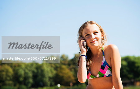 Girl using Cell Phone at Beach, Lampertheim, Hesse, Germany Stock Photo - Premium Royalty-Free, Image code: 600-07117299