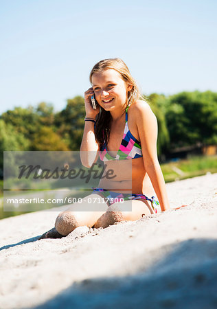 Girl using Cell Phone at Beach, Lampertheim, Hesse, Germany Stock Photo - Premium Royalty-Free, Image code: 600-07117300