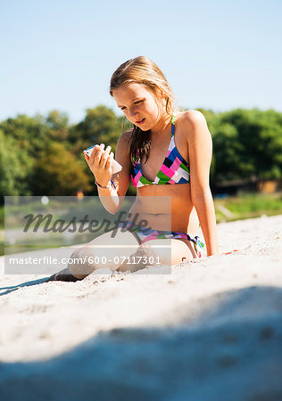 Girl using Cell Phone at Beach, Lampertheim, Hesse, Germany Stock Photo - Premium Royalty-Free, Image code: 600-07117301