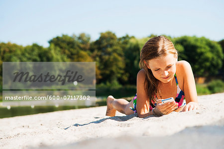 Girl using Cell Phone at Beach, Lampertheim, Hesse, Germany Stock Photo - Premium Royalty-Free, Image code: 600-07117302