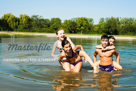 Kids Giving Piggy Back Rides in Lake, Lampertheim, Hesse, Germany Stock Photo - Premium Royalty-Free, Image code: 600-07148099