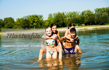 Kids Giving Piggy Back Rides in Lake, Lampertheim, Hesse, Germany Stock Photo - Premium Royalty-Free, Image code: 600-07148100