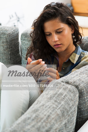 Teenage girl sitting on sofa looking at smart phone, Germany Stock Photo - Premium Royalty-Free, Image code: 600-07148156