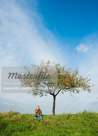 Farmer sitting on hill next to apple tree, eating apple, Germany Stock Photo - Premium Royalty-Free, Image code: 600-07148343