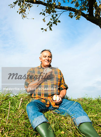 Portrait of farmer sitting in field eating apple, Germany Stock Photo - Premium Royalty-Free, Image code: 600-07148344