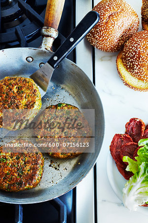 Chickpea falafel burgers in frying pan on stove, studio shot Stock Photo - Premium Royalty-Free, Image code: 600-07156123