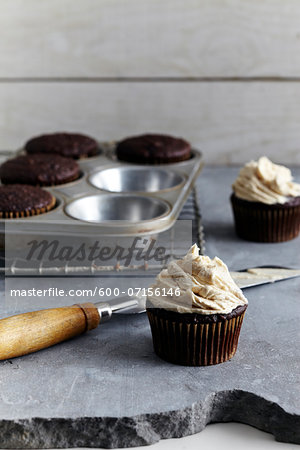 Frosting freshly made cupcakes, studio shot Stock Photo - Premium Royalty-Free, Image code: 600-07156146