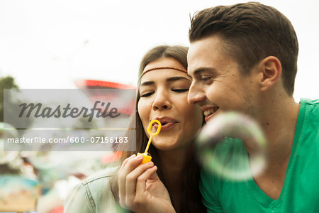 Close-up portrait of young couple blowing bubbles at amusement park, GermanyYoung Stock Photo - Premium Royalty-Free, Image code: 600-07156183