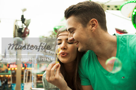 Close-up portrait of young couple blowing bubbles at amusement park, Germany Stock Photo - Premium Royalty-Free, Image code: 600-07156184