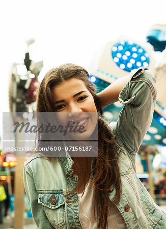 Close-up portrait of teenage girl at amusement park, looking at camera and smiling, Germany Stock Photo - Premium Royalty-Free, Image code: 600-07156187