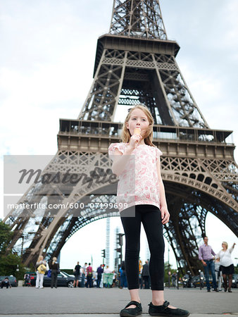 Girl eating Ice Cream Cone in front of Eiffel Tower, Paris, France Stock Photo - Premium Royalty-Free, Image code: 600-07199699