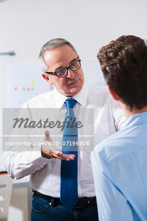Businessman explaining work to apprentice in office, Germany Stock Photo - Premium Royalty-Free, Image code: 600-07199806