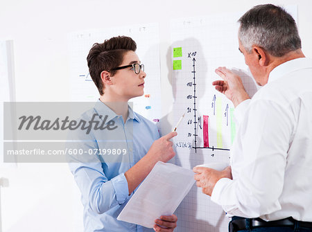 Businessman explaining chart to apprentice in office, Germany Stock Photo - Premium Royalty-Free, Image code: 600-07199809