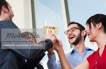Business people holding champagne glasses and toasting each other in office, Germany Stock Photo - Premium Royalty-Free, Image code: 600-07199921