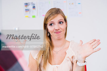 Close-up of young, blond businesswoman making hand gesture in meeting in office, Germany