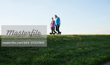 Couple Walking Dog Outdoors, Mannheim, Baden-Wurttemberg, Germany Stock Photo - Premium Royalty-Free, Image code: 600-07237892
