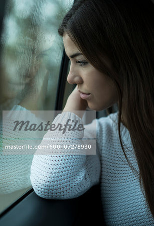 Portrait of young woman sitting inside car and looking out of window and day dreaming on overcast day, Germany Stock Photo - Premium Royalty-Free, Image code: 600-07278930