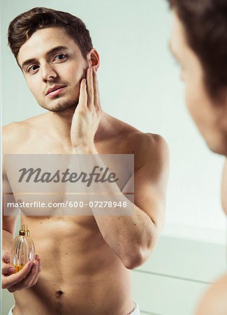 Close-up of young man looking in bathroom mirror applying cologne to face, studio shot Stock Photo - Premium Royalty-Free, Image code: 600-07278948