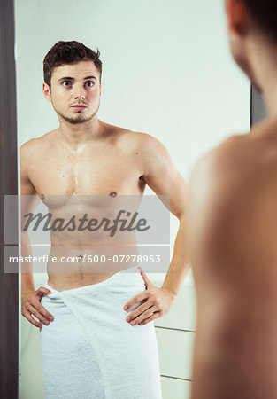 Portrait of young man with towel wrapped around waist, looking in bathroom mirror, studio shot Stock Photo - Premium Royalty-Free, Image code: 600-07278953