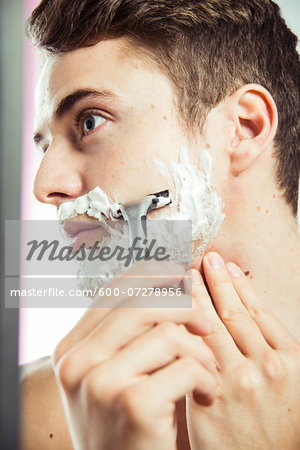 Close-up of young man shaving face with razor, studio shot Stock Photo - Premium Royalty-Free, Image code: 600-07278956