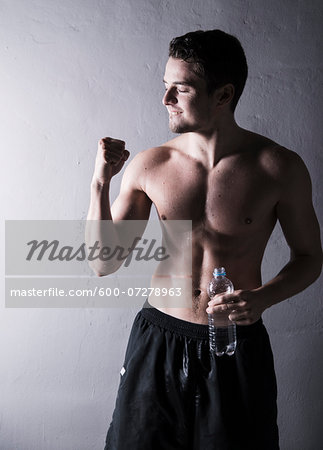 Young man pumping fist and holding bottle of water after working out, studio shot on grey background Stock Photo - Premium Royalty-Free, Image code: 600-07278963