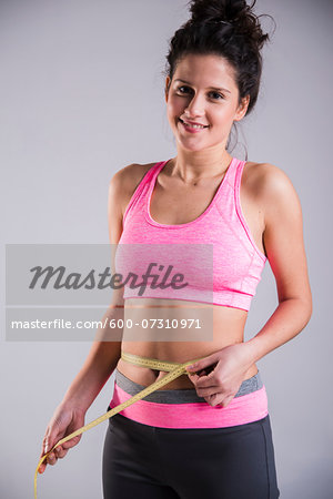 Portrait of Teenager Measuring Waist Stock Photo - Premium Royalty-Free, Image code: 600-07310971